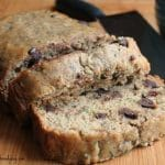 close up of sliced chocolate chip zucchini banana bread on wooden cutting board