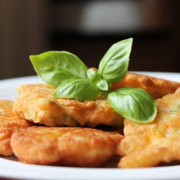 close up of fried squash blossoms on plate with fresh basil on top