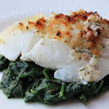 lemon baked cod topped with crumbs on spinach