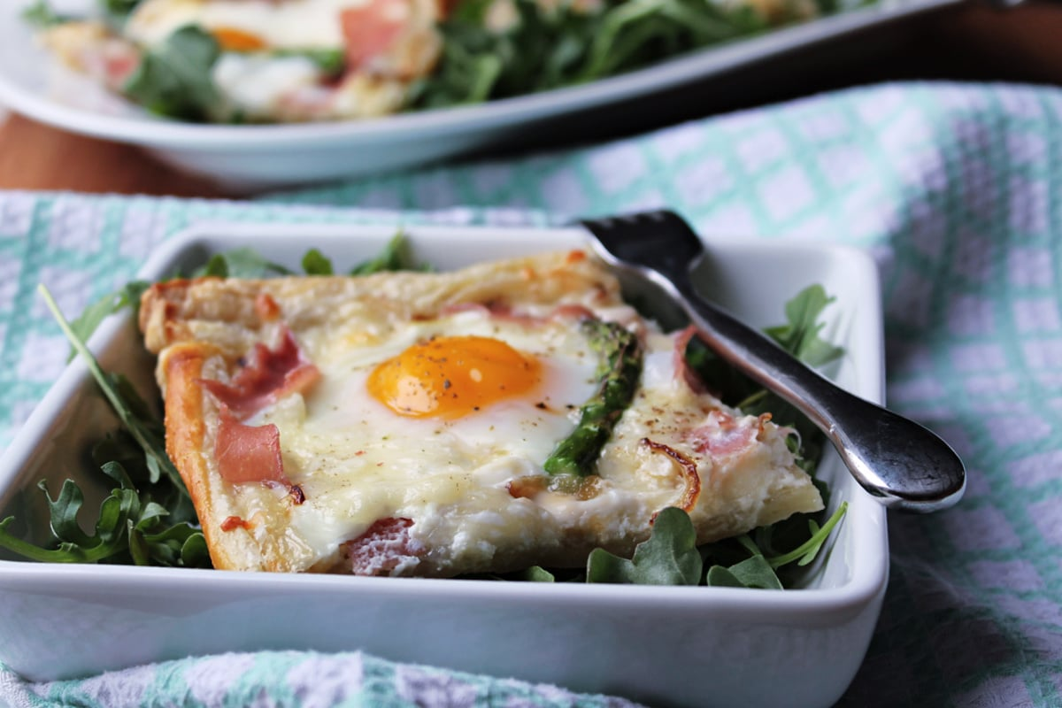 square of egg tart on leafy greens in a square white plate