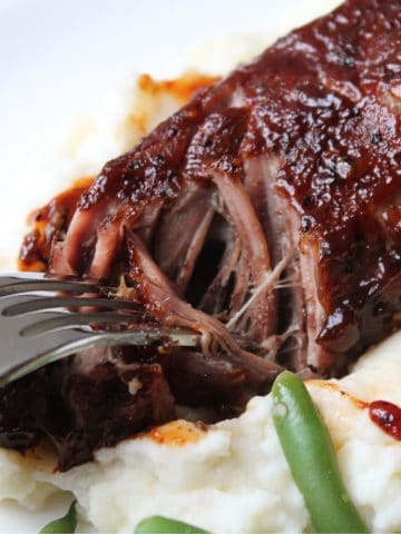 close up of fork breaking up country style beef rib on plate