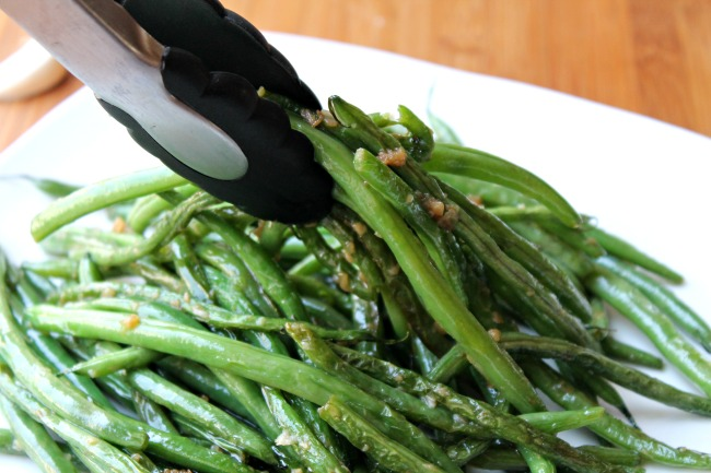 green bean recipe served with tongs