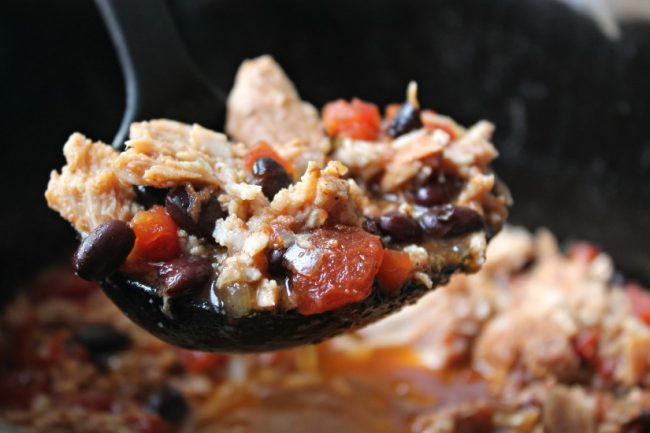 slow cooker pork chili in a ladle