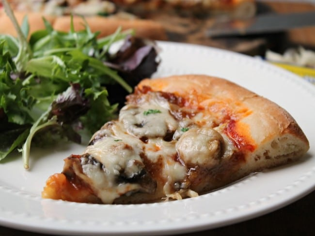 caramelized onion and mushroom pizza plated with salad