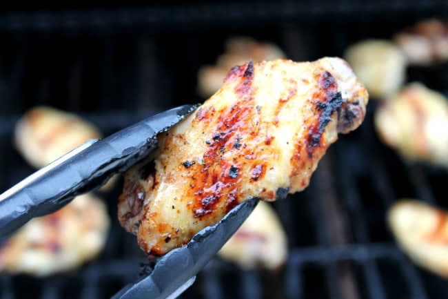 grilled chicken wing held with tongs