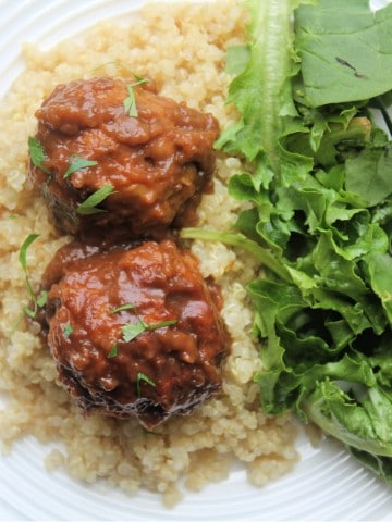 air fryer meatballs cooked on plate with quinoa, gravy and salad