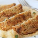 crispy pork sliced with polenta on a white plate close up