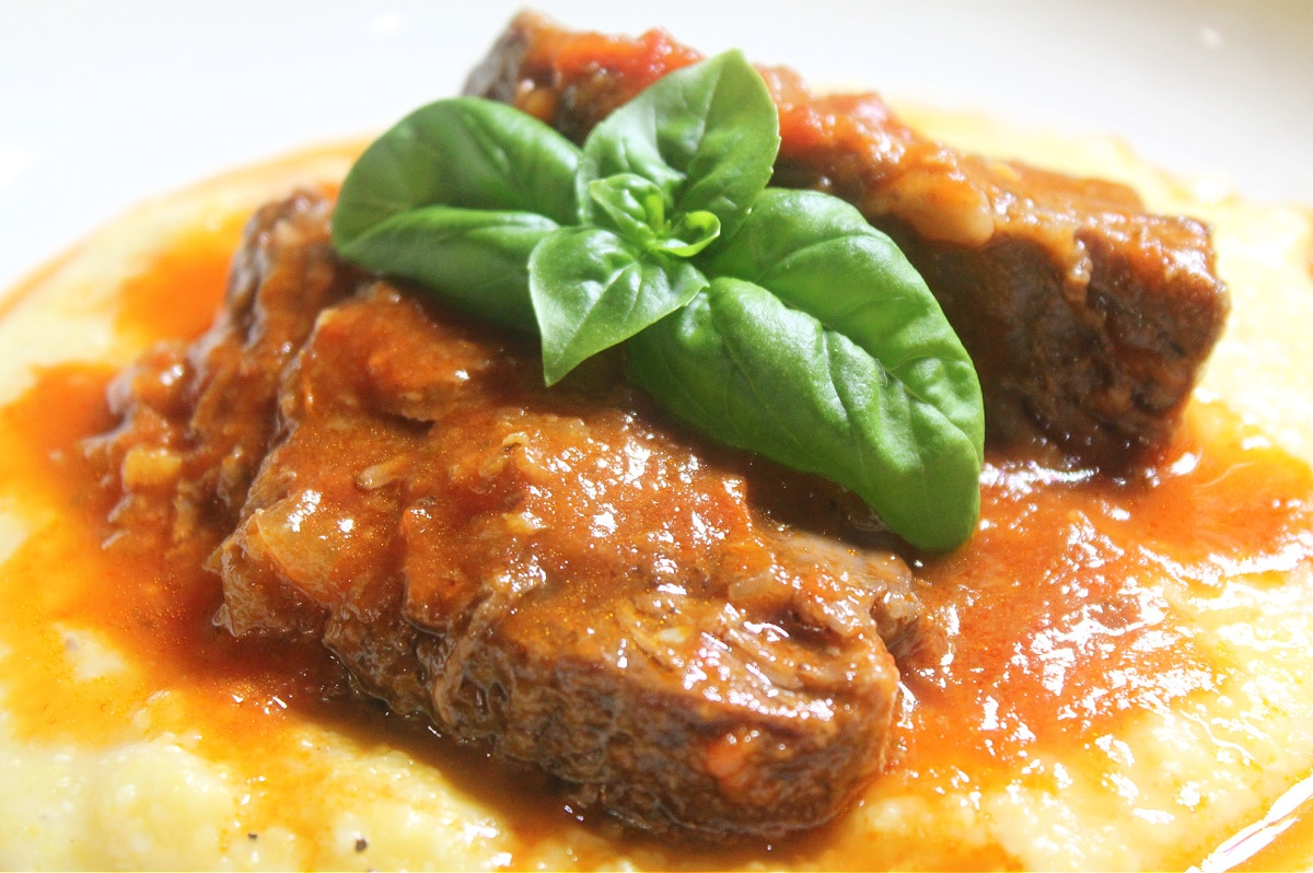 Italian Pot roast, cooked, sliced and served over polenta with basil leaf on top