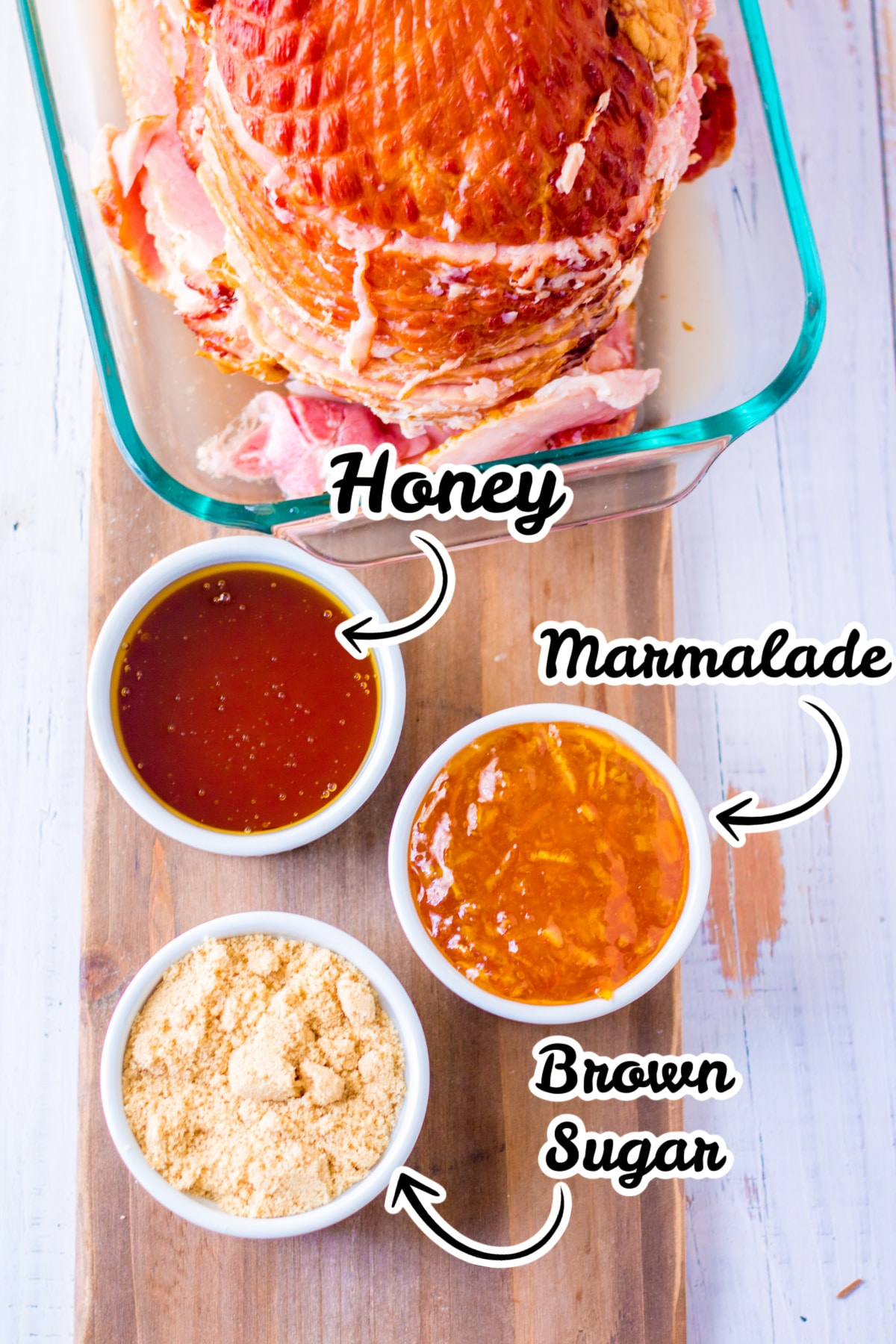 ham in baking dish and ingredients in bowls on cutting board