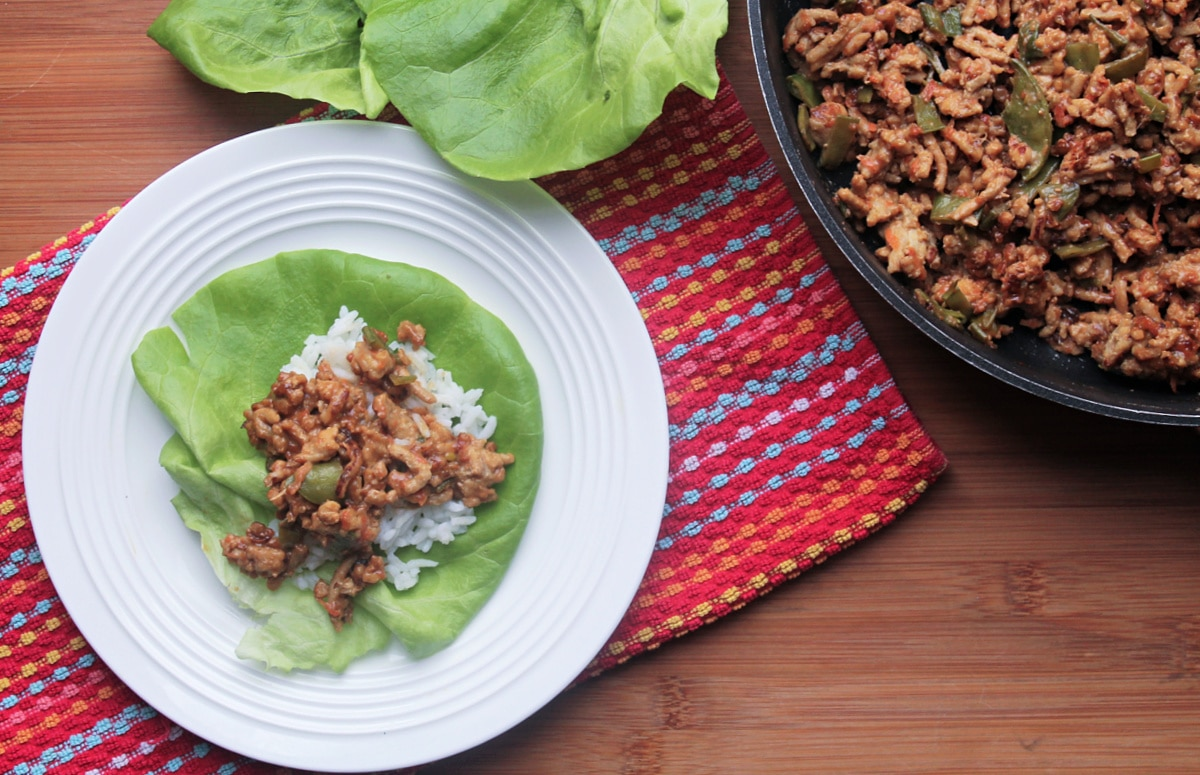 white plate with lettuce wrap assembly ingredients and pan of cooked chicken mixture to the side