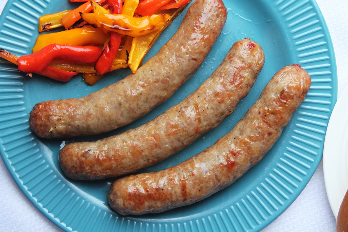 3 cooked sausage links on blue plate with cooked peppers next to them