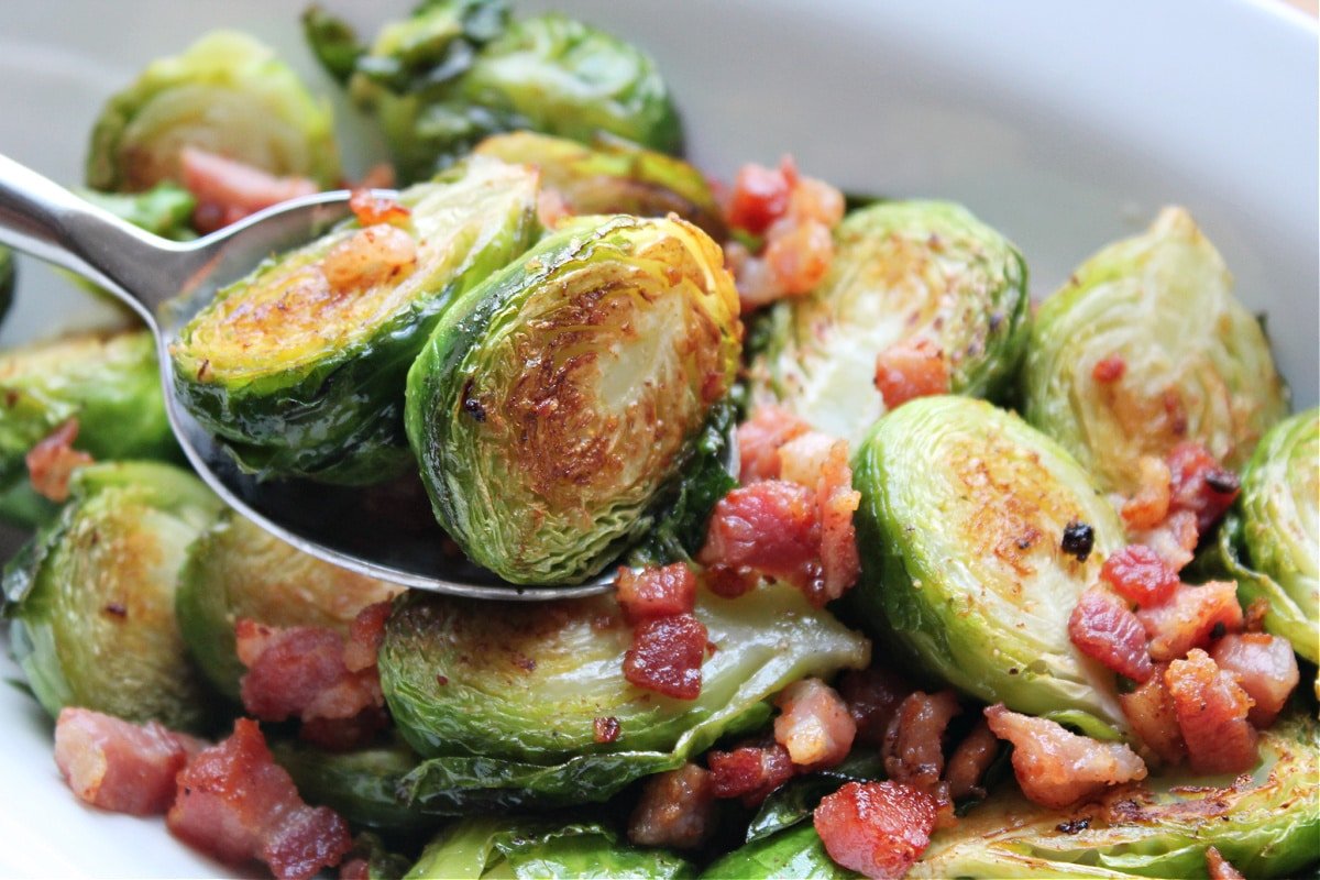 caramelized brussels sprouts in spoon above serving bowl