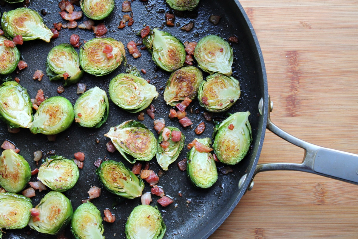 sprouts caramelized cut side up in skillet on cutting board