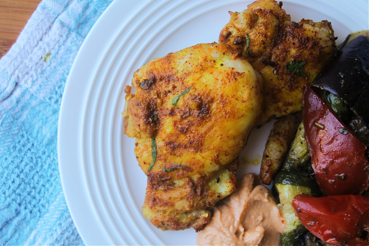 chicken cooked on plate with hummus and grilled vegetables