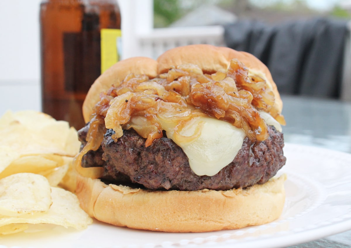 close up of prepared burger on a white plate with a bottle of beer in background
