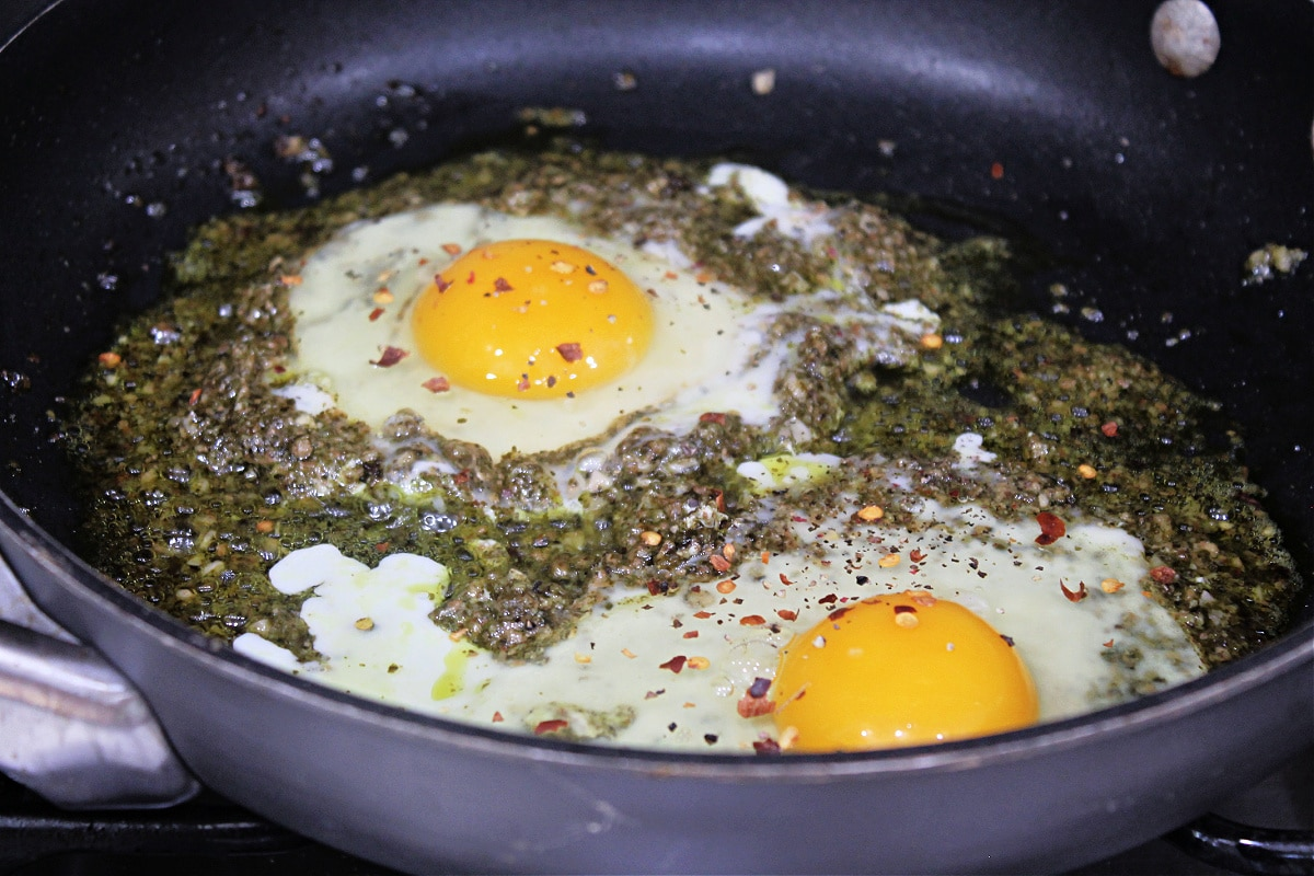 eggs cooking in pesto in a skillet