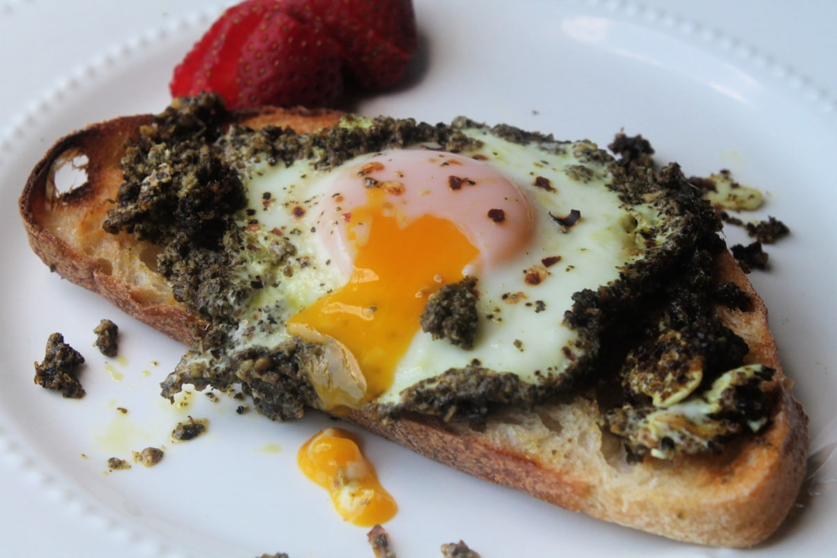 runny egg in pesto on toast served on a white plate with strawberries on the side