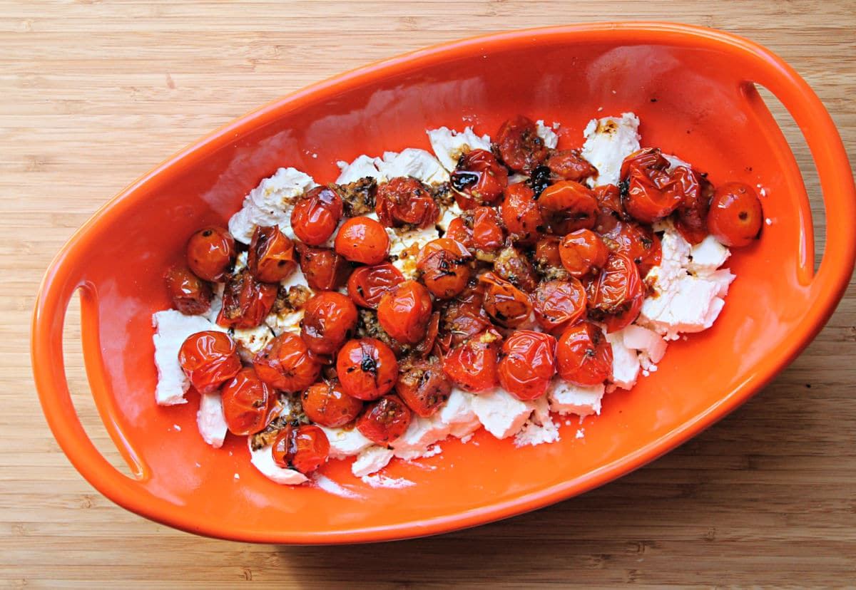 prepared tomatoes placed over goat cheese in baking dish. Dish is on wood cutting board.