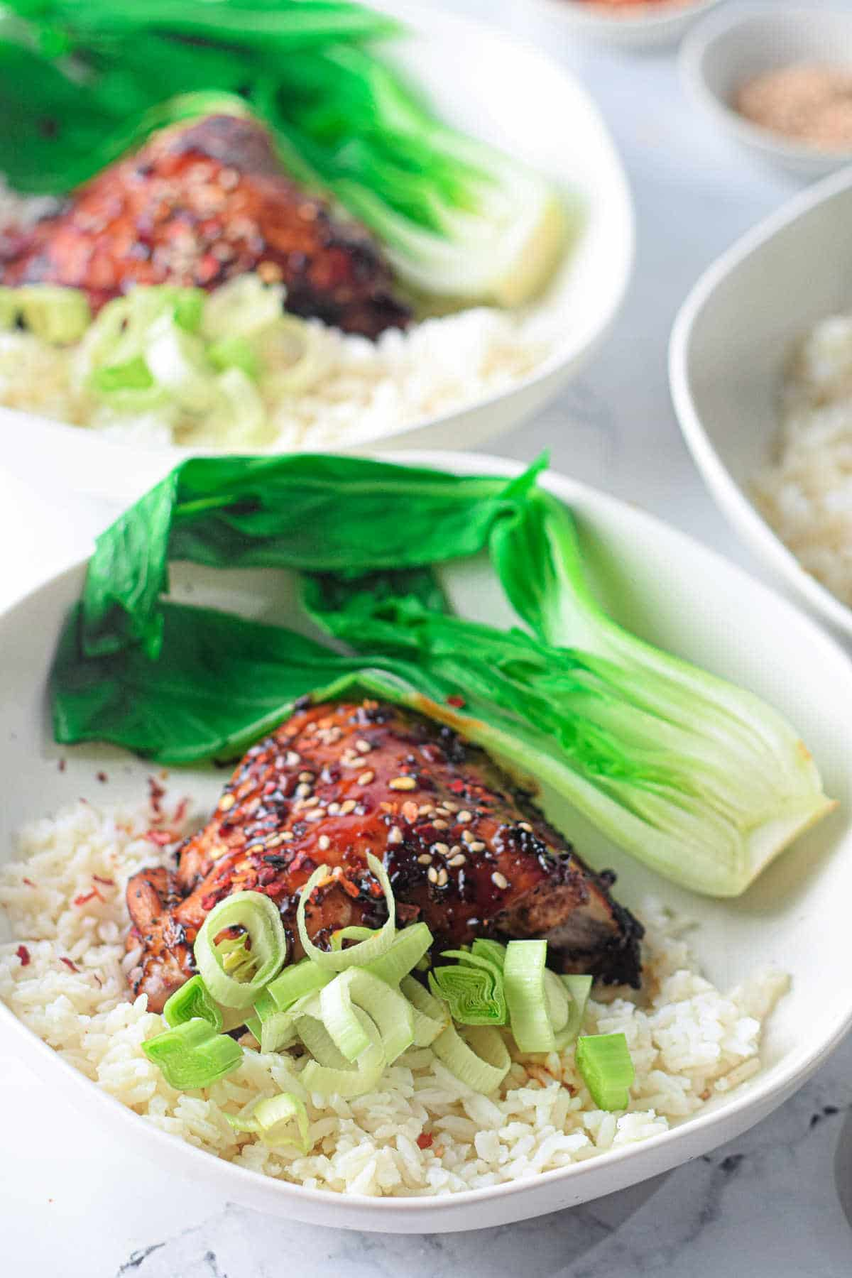 cooked chicken in white bowl with rice and bok choy topped with scallions