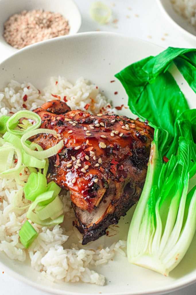 asian glazed chicken on a bed of white rice with bok choy on the side
