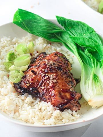 asian-glazed chicken thigh in a white bowl with white rice and steamed bok choy, garnished with sliced green onion