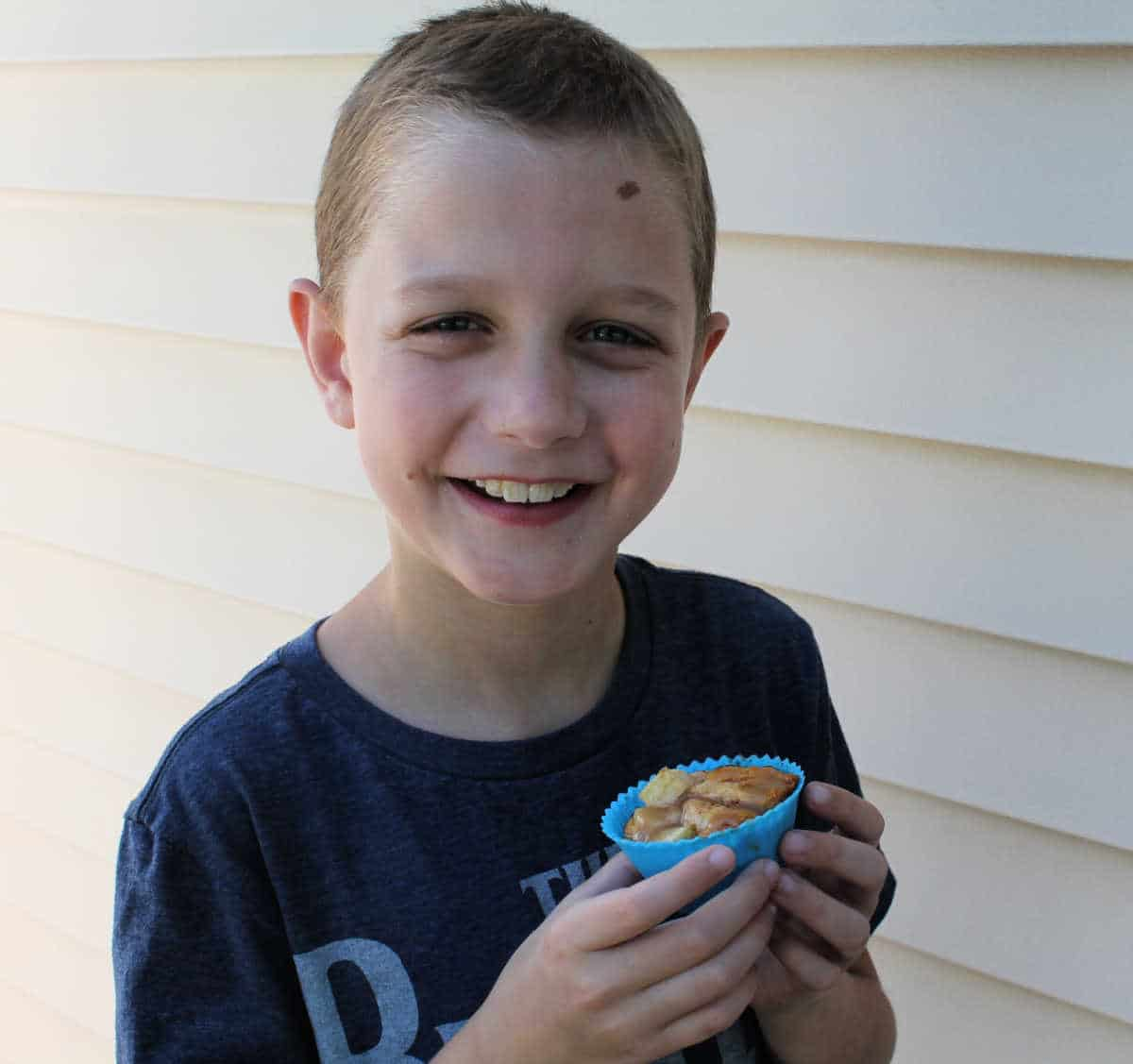 a boy holding an apple cupcake