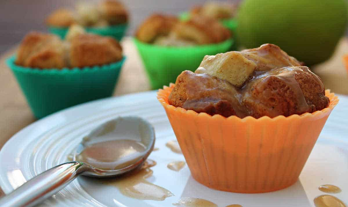 apple monkey bread cupcake plated on a white plate with a spoon covered in glaze next to it