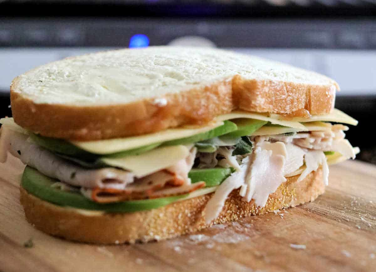 assembled sandwich not yet cooked on wooden board