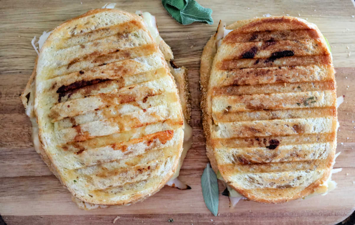 two cooked paninis next to each other on wood board
