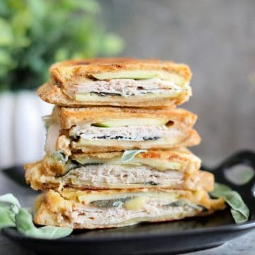 four halves of cooked panini stacked on black square plate