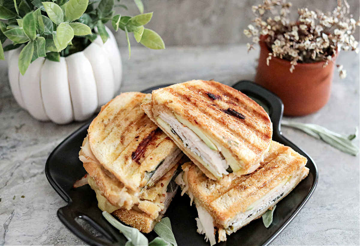 panini halves stacked on a black serving dish with plants in the back for decor