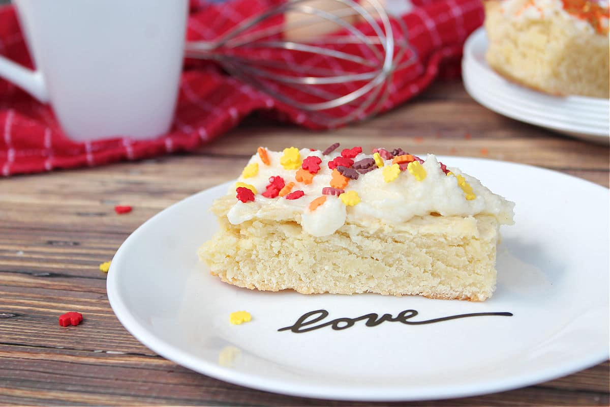 """sugar cookie bar on white plate that says """"love"""". there is a whisk and a coffee mug in the background."""